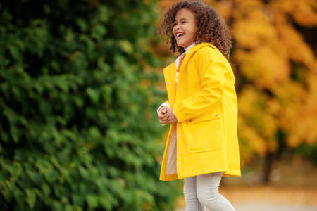 Portrait of cute adorable little girl child making funny silly faces, showing tongue, in autumn fall park outside, playing having fun, lifestyle childhood 스톡 콘텐츠