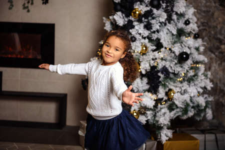 Very nice charming little girl sitting on a child's bed and laughs loudly on the background of Christmas trees in dark interior of the house.