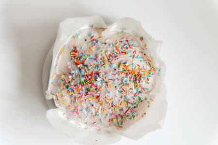 Easter cake, sweet bread decorated with white glaze and colored meringue. Kulich wrapped in a craft paper on the white background. 스톡 콘텐츠