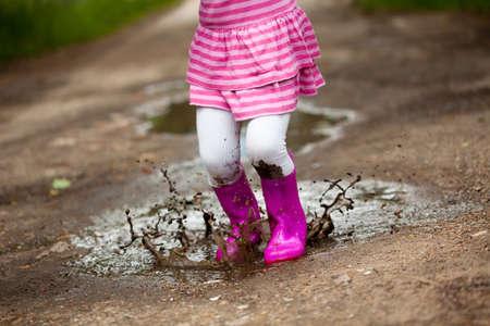 Klein meisje in een plas Stockfoto