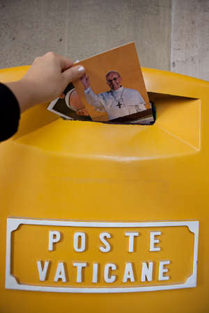 VATICAN - October 30: Postcards with an image of Pope Francis are placed into the mailbox in Vatican on October 30, 2013. Poste Vaticane is an organization responsible for postal service in Vatican City.