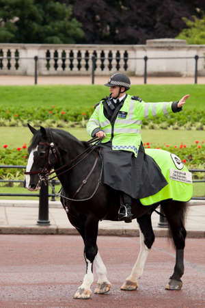London, United Kingdom - June 11, 2010: Policeman on the horse patrols near Buckingham Palace in front of a crowd waiting for guard change ceremony.