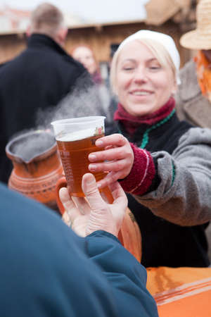 tradespeople: VILNIUS, LITHUANIA - MARCH 7: A woman gives a glass of hot bear during the annual traditional crafts fair - Kaziuko fair on Mar 7, 2009 Editorial