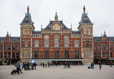 Amsterdam, Netherlands - October 26: People in front of the Central Station building in Amsterdam, Netherlands, on October 26, 2014.