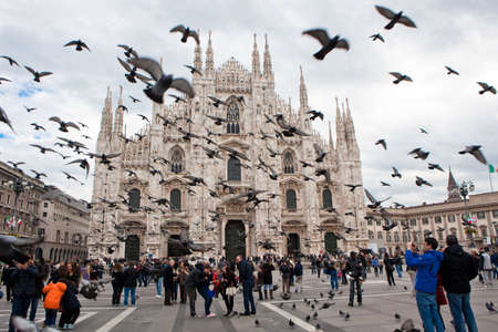 MILAN - NOV 3: Tourists visit the largest cathedral in Italy, Duomo di Milano while a flock of pigeons flies overhead surprisingly on November 3, 2012 in Milan. Gothic Milan Cathedral is a main landmark of the city. Editoriali