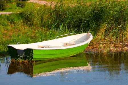 green boat: Green boat on the shore of a lake Stock Photo