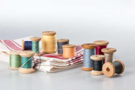 Carretes de hilo con la aguja y el algodón del paño Foto de archivo - 33693003