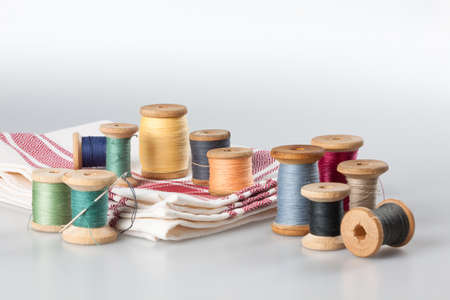 Spools of thread with needle and cotton cloth photo