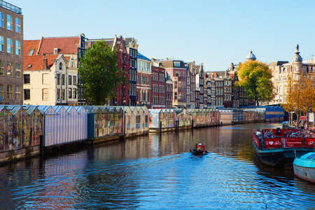 Amsterdam, Netherlands - October 27: Typical Dutch canal located behind the flower market in Amsterdam, Netherlands on October 27, 2014.