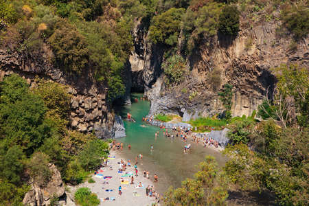 Alcantara, Italy - August 26, 2013: People enjoy ice-cold water of Alcantara river in the Alcantara river park on August 26, 2013 in Sicily Island, Italy.