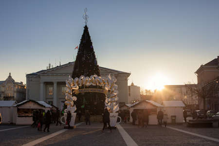 town hall square: Vilnius, Lithuania - December 26, 2014: People walking around the Christmas tree of Vilnius Town Hall on December 26, 2014 in Vilnius, Lithuania. Traditional christmas market is located also in the Town Hall Square.