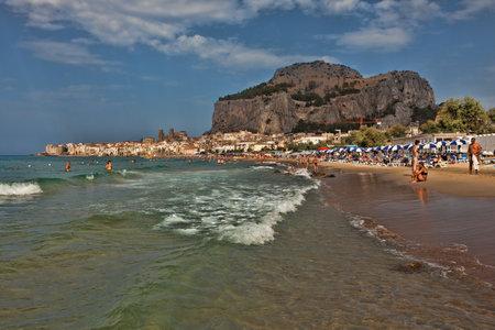 tyrrhenian: Cefalu, Italy - August 27, 2013: People sunbathing on the beach and swimming in Tyrrhenian sea on August 27, 2013 in Cefalu, Italy. Editorial