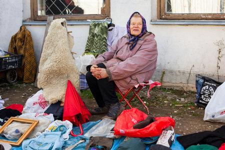 fleamarket: Vilnius, Lithuania - October 11, 2014: Senior woman is selling antique goods in a flea market in Kalvariju marketplace on October 11, 2014 in Vilnius, Lithuania.