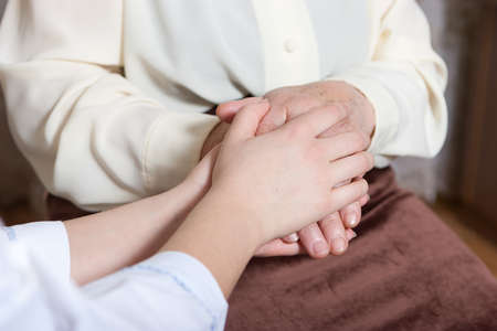 gerontology: Helping hands: the nurse holds hands of the elderly female