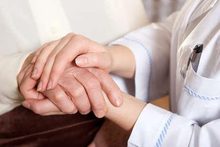 Helpende handen: de verpleegkundige houdt handen van de bejaarde vrouw