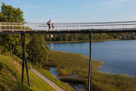 atraction: Zarasai, Lithuania - July 25, 2015: Tourists are visiting Zarasas lake observation bridge and watershore of Zarasas lake on July 25, 2015 in Zarasai, Lithuania