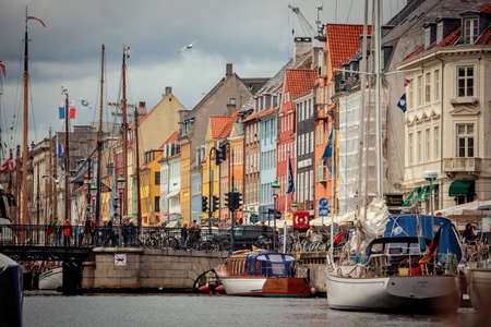 entertainment district: Copenhagen, Denmark - July 29, 2015: People are walking in Nyhavn, a 17th-century waterfront and entertainment district with brightly coloured townhouses, bars, cafes and restaurants.