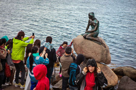 Copenhagen, Denmark - 29 July, 2015: Tourists take pictures of the Little Mermaid statue during rain in Copenhagen, Denmark.