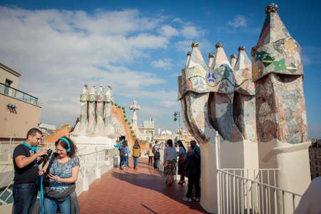 Barcelona, Spain - October 27, 2015: Tourists watch colorful chimneys on the roof of Casa Batllo, one of Antoni Gaudi�s architectural masterpieces in Barcelona.