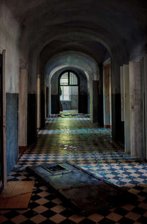 or shatter: Abstract image of a dark spooky corridor in an old abandoned hospital buiding with shatter on the checkered floor Stock Photo