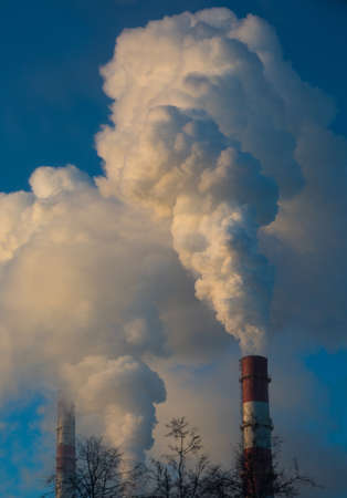 Smoke from industrial chimneys at dawn in the city. Frosty winter day. Stock Photo