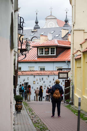 mounted: Vilnius, Lithuania - June 25, 2017: Tourists walk on Literatu street in Vilnius, attractive place of old town. Artworks mounted on the walls of this street dedicated to the literature workers: writers, poets, translators.