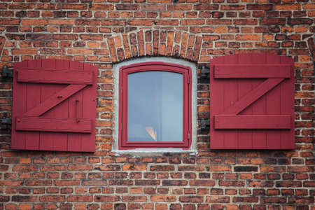 Red brick wll with an oldfashioned window in Copenhagen, Denmark