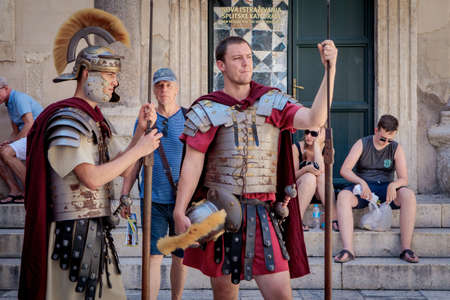 Split, Croatia - August 19, 2017: Street performers in Diocletians Palace. Men wear uniforms of the ancient Rome legionary soldiers.
