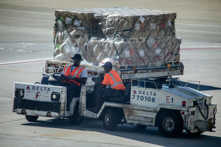 Atlanta, Georgia, USA - October 13, 2016: Dolly fleet operators with the dollies for baggage unit load devices at busy Hartsfield-Jackson Airport.