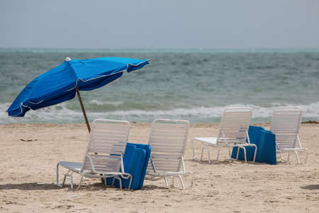 Blue umbrellas and white lounge chairs in the trendy and popular South Beach in Miami, USA