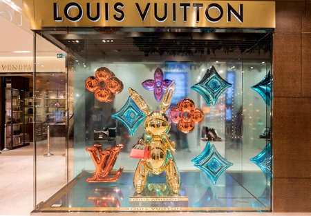 Paris, France - October 30, 2017: Showcase of famous designer bag brand Louis Vuitton in Printemps shopping centre in Paris. Festive christmas decorations are made by an artist Jeff Koons.