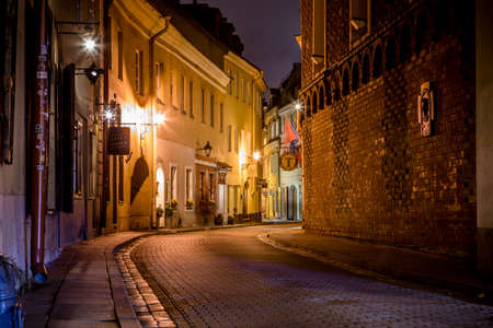 Vilnius, Lithuania - November 7, 2017: Picturesque narrow street of Vilnius old town at night.
