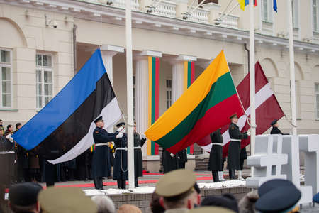 Vilnius, Lithuania - February 16, 2018:  Raising the flags of the three Baltic States  during a state ceremony outside the Presidential Palace to mark the 100th anniversary of the restoration of Lithuanian statehood.