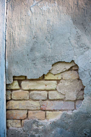 Old vintage yellow brick wall with crumbled plaster layer
