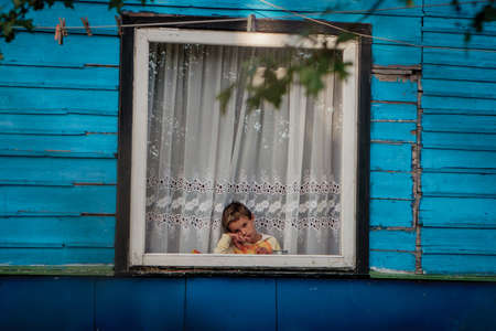 Vilnius, Lithuania - June 28, 2008: Young gypsy girl looks sadly through the window in the Roma encampment (Gypsy tabor) of Vilnius.