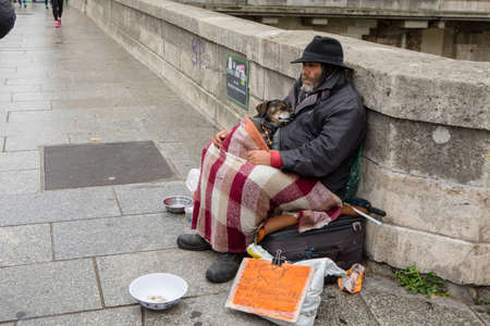 Paris, France - October 29, 2017: A homeless man sits on the street with a dog and asks for help. On the plate is written in french:
