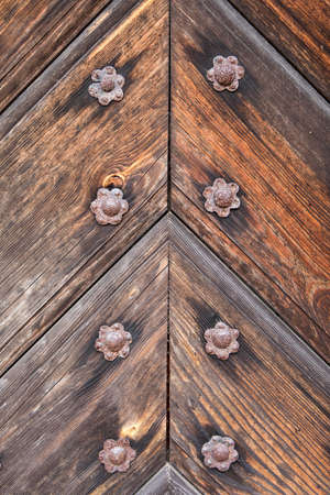 Detail of the old wooden door with rusted iron studs