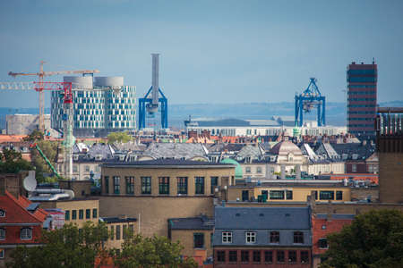 Copenhagen, Denmark - July 29, 2015: Copenhagen cityscape with modern industrial buildings in the distance.