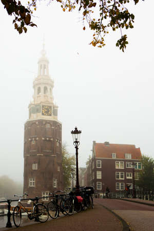 Amsterdam, Netherlands - October 28, 2014: Foggy morning in Amsterdam. View of a canal in the old city of Amsterdam.