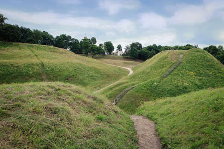 Kernave, Lithuania - June 25, 2011: Tourists climb on mound hills in Lithuanian historic capital Kernave, UNESCO World Heritage Site.