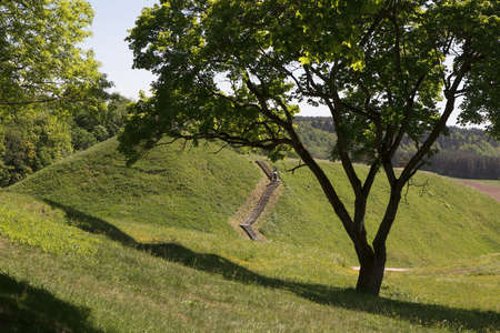 Kernave, Lithuania - May 27, 2017: Tourists climb on mound hills in Lithuanian historic capital Kernave, UNESCO World Heritage Site.