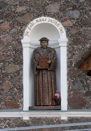 Taurage, Lithuania - November 4, 2005: Statue of Martin Luther in the niche of the facade of a church. Sculptor Antanas Bagdonas. Text in Lithuanian: They have to leave us the word...