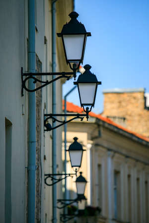 Row of street lamps on the wall of Vilnius old town, Lithuania Stock Photo