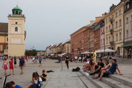 Warsaw, Poland - August 10, 2018: Street musician performs in the Royal Castle square in Warsaw, Poland on a warm summer evening.