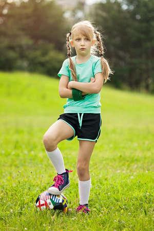 Mädchen, das Fußball auf der Wiese spielt