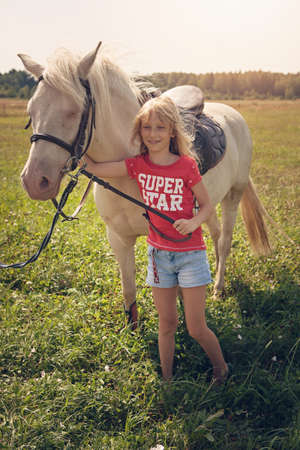 A young girl and white pony horse in countryside, Lithuania