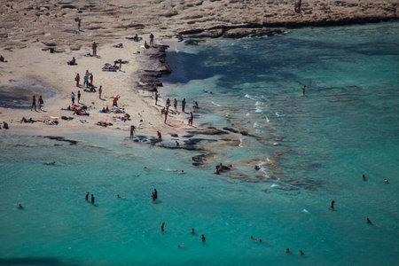 Balos, Greece - August 22, 2011: Balos lagoon on Crete island, Greece. Tourists relax and bath in crystal clear water of Balos beach.