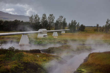 Geothermal power station in Iceland. Generation of ecologically clean renewable energy. Landscape of geothermal sources and geothermal energy plant. 스톡 콘텐츠