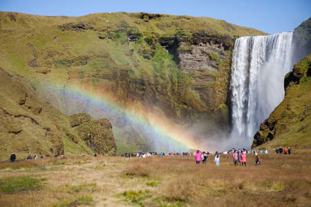 Skogafoss, Iceland - September 5, 2018: Tourists were scatterred around the huge iconic Skogafoss waterfall. Visible rainbow near the waterfall. Focus on the waterfall. Editorial