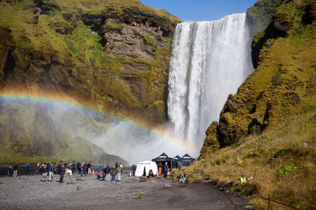 Skogafoss, Iceland - September 5, 2018: Tourists were scatterred around the huge iconic Skogafoss waterfall. Visible rainbow near the waterfall. Editorial